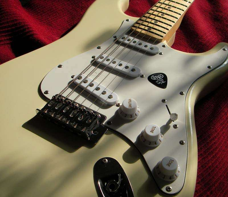 Close up of guitar body in cream with white pick guard.